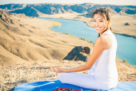 Happy asian woman relaxing and meditating outdoor at mountain above Ili river valley at Kazakhstan. She sits at peak in lotus position and feel harmony of your body and nature. Healthy lifestyles concept of body and soul