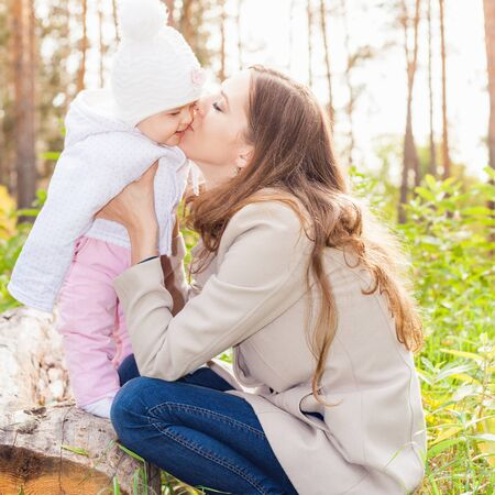 mothercare: Happy mother kissing her baby at outdoor, wearing a autumn coat. Mothercare is most important in baby life