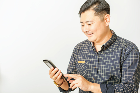 utility payments: asian businessman using a mobile phone or tablet pc at white background for any text. Its can be used for business and wireless technology, internet or utility payments Stock Photo