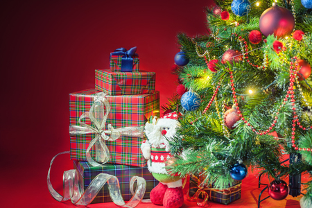 christmas tree presents: Decorated christmas tree with gift boxes and Santa Clus toy at red background, copy space. Concept of family gifts and presents at christmas eve and New Year Stock Photo