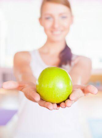 abdomen plano: concepto de estilo de vida saludable con una hermosa mujer vestida de blanco Holdin una gran manzana verde. alimentación vegetariana y la dieta buena para su peso y un vientre plano. enfoque selectivo en la manzana.