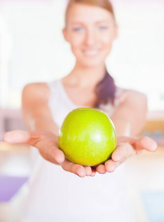 flat stomach: Healthy lifestyle concept with beautiful woman dressed in white holdin a big green apple. Vegetarian eating and diet good for your weight and a flat stomach. Selective focus at apple. Stock Photo