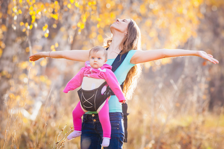 ergonomic: Happy mother carrying her child by ergonomic baby carrier. They walk outdoor at national mountain park at autumn season