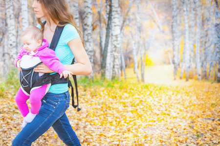ergonomic: Closeup mother carrying her child by ergonomic baby carrier. They walk outdoor at national mountain park at autumn season. Travel with baby concept