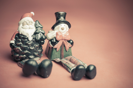 christmas toy: Christmas toy of Santa Claus and snowman sitting together at red background at Christmas eve
