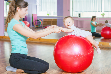 Mother with happy baby doing exercises with red gymnastic ball at fitness class. Concept of caring for the baby's health.