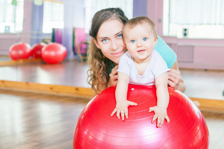 infant: Mother with happy baby doing exercises with red gymnastic ball at fitness class. Concept of caring for the babys health.