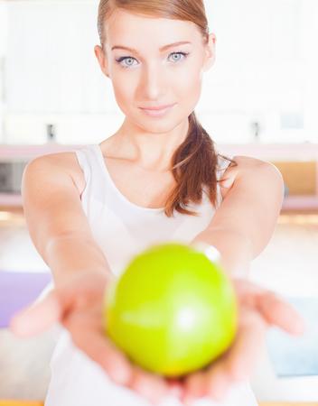 abdomen plano: Concepto de estilo de vida saludable con hermosa mujer vestida de blanco la celebración de una gran manzana verde. Alimentación vegetariana y la dieta buena para su peso y un vientre plano.