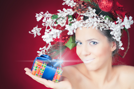 christmas shopping: Christmas shopping with winter woman, tree hairstyle and makeup for holiday giving for you present or gift box! Magical lights star. Beauty fashion model. Red background. New Year or Halloween style