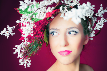 makeup: Christmas winter woman with tree hairstyle and makeup for holiday night. Beauty fashion model with white lips and pink background. Frozen fairy blue eyes like a piece of ice! New Year or Halloween style