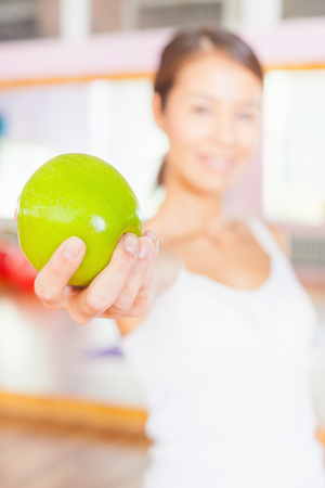 flat stomach: Healthy lifestyle concept with beautiful asian woman dressed in white holding a big green apple. Vegetarian eating and diet good for your weight and a flat stomach. Selective focus at apple. Stock Photo