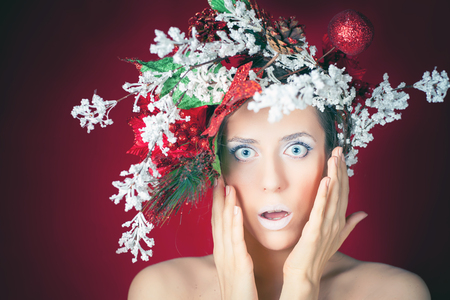 young tree: Surprised Christmas winter woman with tree hairstyle and makeup for holiday night. Beauty fashion model with white lips and pink background. Frozen fairy blue eyes like a piece of ice! Stock Photo