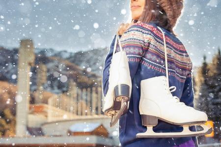 salud y deporte: Mujer asi�tica feliz que va al patinaje de hielo al aire libre. Ella vestida con jersey y gorro. Holding patines zapatos. estilo de vida saludable y el deporte concepto en el estadio. El clima de invierno con nieve tormenta de nieve