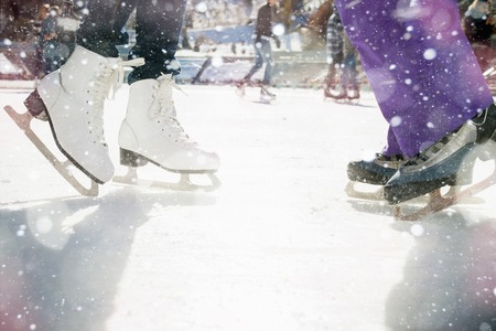Closeup skating shoes ice skating outdoor at ice rink. Magical glitter of snowy snowflakes and bokeh. Healthy lifestyle and winter sport concept at sports stadium. Stockfoto