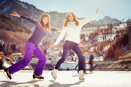 Image of group funny teenagers girls ice skating outdoor at ice rink, posing and looking at camera. Medeo stadium. Almaty. Winter activities for good mood and healthy mind. Healthy lifestyle and sport
