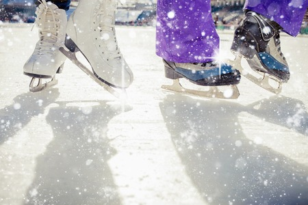 ice cold: Pair is placed on ice skating. It is snowing outside. Skating close-up. Medeo, Kazakhstan