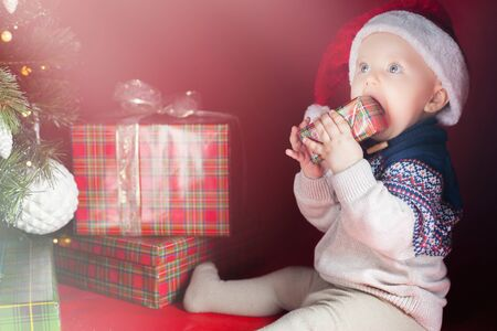 surprised baby: Happy surprised baby holding gift box or present at Christmas night, eve! Kid dressed in red Santa hat. Xmas and New Year holiday!