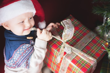 not open: Christmas holiday. Baby in Santa hat opening a box of gifts. Sitting under the tree on a red background. Angry and nibbles tape. Can not open. New Year. Night