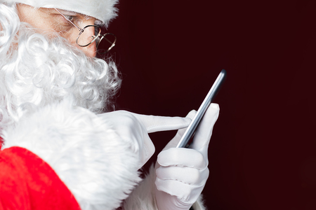 Santa Claus using a mobile phone at Christmas time. Santa typing message or sms to Elf or Dwarf. Luxory Cristmas gift or present for your good behavior! New Year. Copy space for disign, text