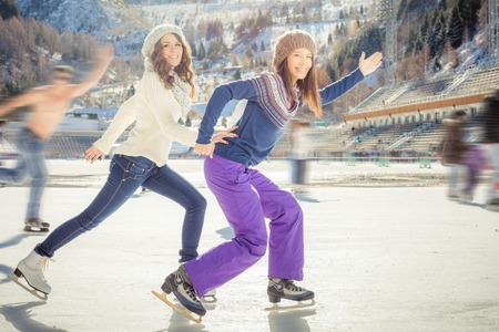 Image of group funny teenagers ice skating outdoor at ice rink, holding hands at Medeo stadium. Winter activities for a good mood and healthy mind. Action and speed Stockfoto