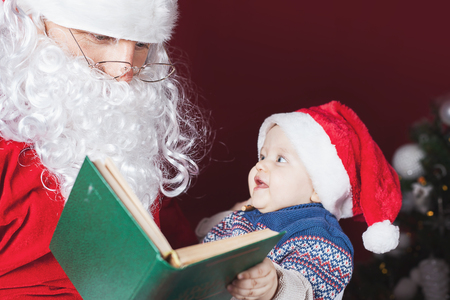 santa: Santa Claus reading a book with christmas fairy tale. Baby looking at Santa surprised. Boy or Girl dressed in red hat. Funny child