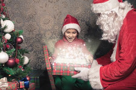 surprise box: Happy shocked boy surprised to see Santa Claus! Child dressed in red Santa hat. Surprise! Xmas and New Year holiday. Your dad dressed in a Santa Claus costume! Christmas inspiration