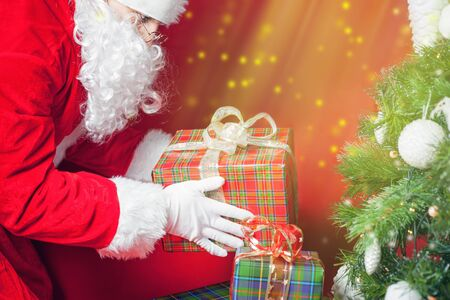 under a tree: Christmas light and inspiration! Santa Claus putting gift box or present under Christmas tree at eve night. Surprise! Xmas and New Year holiday! Red background Stock Photo