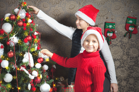 home decorating: Happy child, boy and girl decorating a christmas tree at home. Concept of traditional world celebration. Holiday, New Year, Gifts
