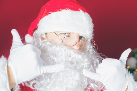 cool guy: Cool and funny Santa Claus at red background. Christmas and party concept. New Year holiday. Shopping discount. Design