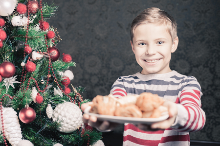christmas baker's: Handsome boy giving to Santa Claus cookies at Christmas holiday. Plate of biscuits, sweet baking. Decorated Christmas tree at living room Stock Photo