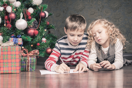 christmas list: Boy and girl lying on the floor under the Christmas tree. Next to the gifts. They are writing wishlist for Santa. Waiting for Christmas. Celebration. New Year.