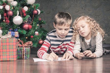 persona escribiendo: Ni�o y ni�a tendido en el suelo debajo del �rbol de Navidad. Al lado de los regalos. Est�n escribiendo deseos para Santa. Esperando la Navidad. Celebraci�n. A�o nuevo.