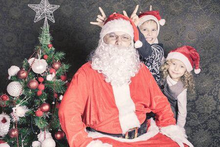 fiesta familiar: Familia divertida, ni�os felices y Santa Claus! Mostrar cuernos. Sentado en su casa cerca de una decoraci�n del �rbol de Navidad. Ni�o y ni�a vestida de rojo sombrero de Santa. Concepto de la celebraci�n tradicional del mundo, d�a de fiesta