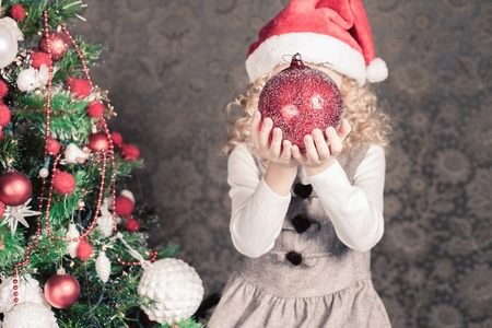 home decorating: Funny girl decorating a christmas tree at home. Holding big red decoration ball. Holiday concept, New Year, gift