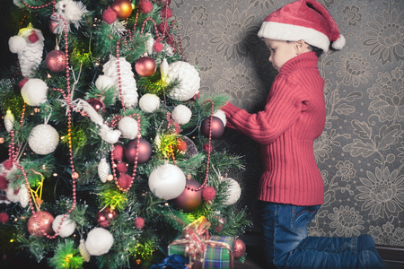 home decorating: Happy boy decorating a christmas tree at home. Concept of traditional world celebration. Holiday, New Year, Gifts Stock Photo
