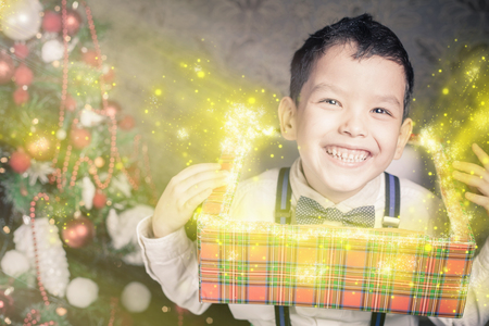 surprise box: Funny surprised boy peek out of the gift box! Christmas tree. Surprise! Xmas and New Year holiday. Christmas inspiration