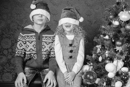 retro revival: Retro image of funny kids with Santa hats at Christmas holiday near decorated christmas tree. New Year. Concept of family celebration. Retro revival, old edition, black and white Stock Photo