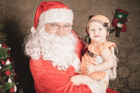 baby near christmas tree: Santa Claus holding baby near christmas tree! Xmas and New Year holiday!
