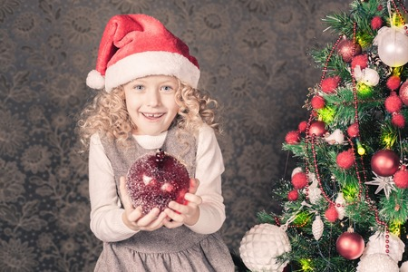 home decorating: Cute girl decorating a christmas tree at home. Holding magical red decoration ball. Holiday concept, New Year, gift Stock Photo