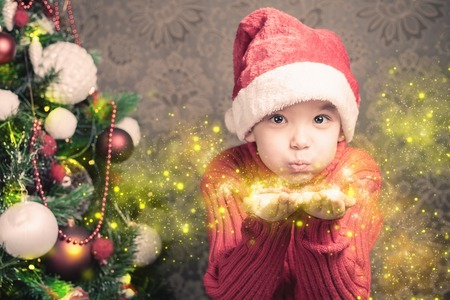 cute fairy: Little boy fairy blowing fairy magical glitter, stardust at Christmas.   Christmas tree. Xmas child and New Year holiday! Merry Christmas your family!