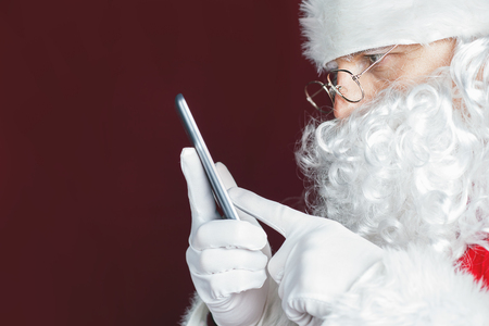 dwarf christmas: Santa Claus using a mobile phone at Christmas time. Santa typing message or sms to Elf or Dwarf. Luxory Cristmas gift or present for your good behavior! New Year. Copy space for disign, text