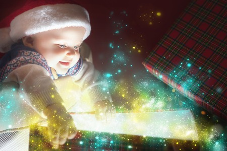 Christmas baby wearing a Santa Claus hat opening a present or gift box! Night, xmas eve, surprise. Magical light. Copy space. Design