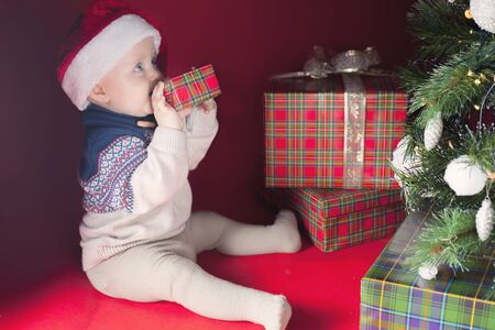 itch: Happy surprised baby holding gift box or present at Christmas night, eve! Kid dressed in red Santa hat. Xmas and New Year holiday! Teeth itch