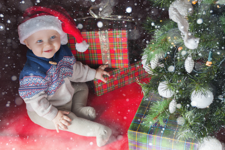 surprised baby: Happy baby surprised near the decorated Christmas tree with many gift and present box! Kid dressed in red Santa hat. Xmas and New Year holiday! Winter, snow