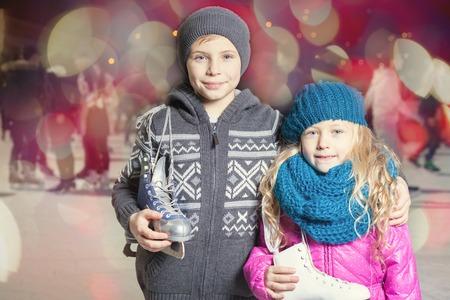 niño en patines: Niños que sostienen patines de hielo zapatos en pista de hielo al aire libre, el deporte y la vida sana de patinaje sobre hielo en el estadio Medeo, Almaty, noche. Los niños lindos, niño y niña mirando a la cámara