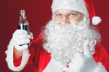 disign: Funny Santa Claus holding Cola fresh beverage at glass bottle. Christmas holiday, New Year. Thumb up gesture. Copy space for disign, text at red background Stock Photo