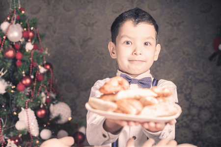 christmas baker's: Handsome asian boy giving to Santa Claus cookies at Christmas holiday. Plate of biscuits, sweet baking. Decorated Christmas tree at living room