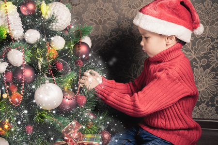 tree decorations: Boy decorating a christmas tree at home. Concept of traditional world celebration. Holiday, New Year