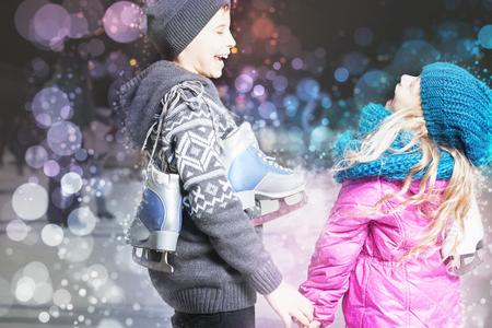 patín: niños divertidos que sostienen los zapatos patines de hielo en la pista de patinaje sobre hielo al aire libre, el deporte y la vida sana patinaje sobre hielo en Holanda, Europa, noche. Los niños lindos, niño y niña laughting