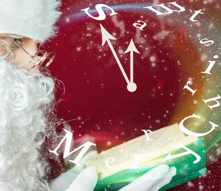 five to twelve: Christmas clock. Midnight, five minutes to twelve. Santa Claus reading a book with fairy tale. Mature man blowing on the text of Merry Christmas that fly with magical glitter and stardust. Stock Photo